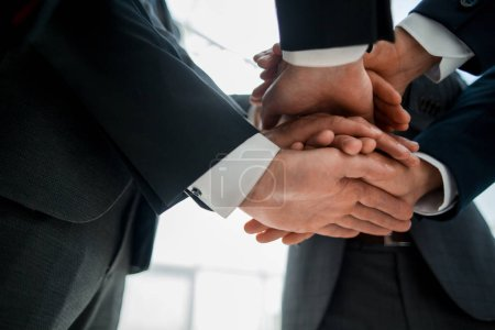 Close-up of businesspeople stacking hands in meeting