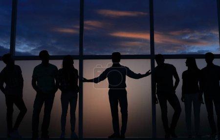 chef de file et un groupe de jeunes gens, debout près d'une grande fenêtre