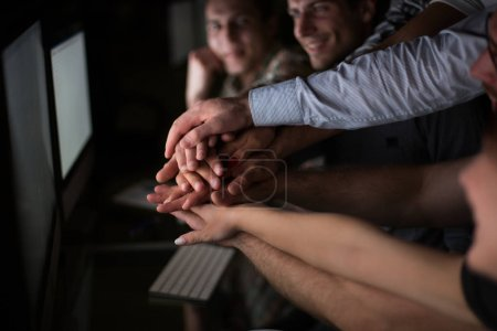 close up.young active office workers hold their hands together