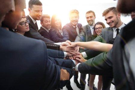 Foto de Concepto de team building. grupo grande de gente de negocios de pie con las manos cruzadas juntas - Imagen libre de derechos
