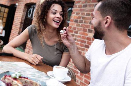 Photo pour Jeune couple dégustant un café dans un café de rue - image libre de droit