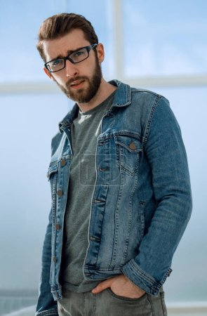 Photo for Side view.fashionable young man in a denim jacket, on the background of the office - Royalty Free Image