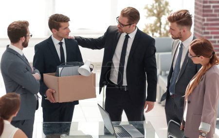 fired employee with personal things saying goodbye to colleagues