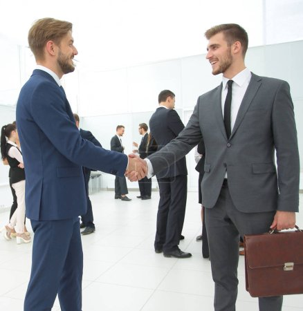 Photo for In the foreground, handshake business partners in the lobby of the office. - Royalty Free Image