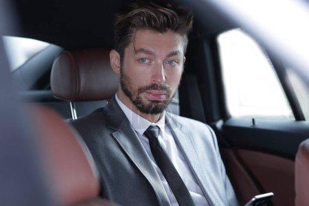 Photo pour Homme d'affaires occasionnel sur téléphone portable à l'arrière de la voiture - image libre de droit