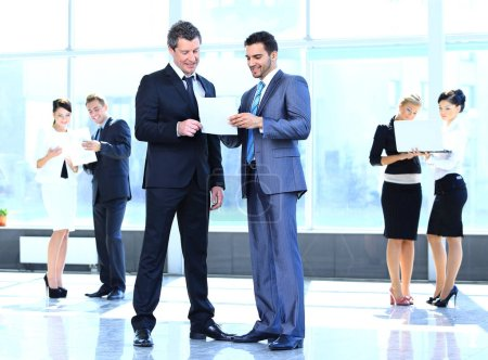Photo for Employees discuss working papers, standing in the lobby of the office - Royalty Free Image