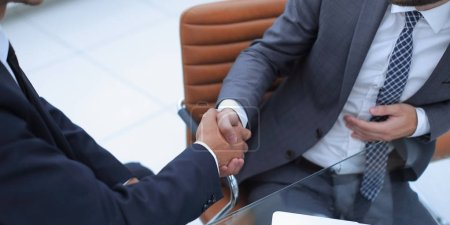 handshake business partners in front of the open laptop