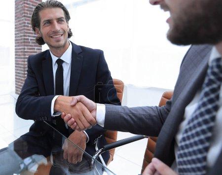Photo pour Vue de dessous. poignée de main confiante de partenaires d'affaires assis à un bureau - image libre de droit