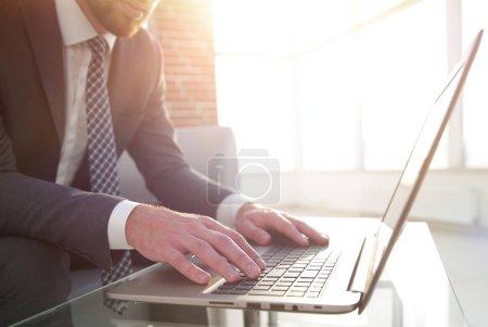 Photo pour Un jeune homme d'affaires concentré tape des informations sur son ordinateur portable au bureau . - image libre de droit