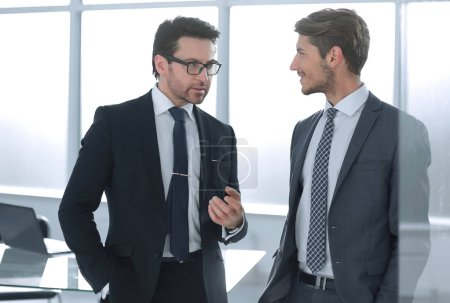 business partners discuss standing in the office