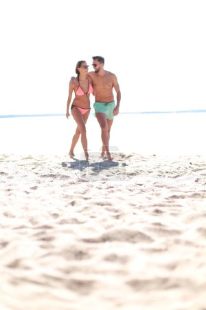 Young couple holding hands and walking on beach.