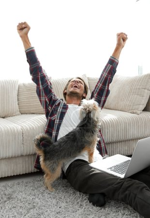 Photo for Happy young man exults with his dog sitting in the living room. the concept of home life - Royalty Free Image
