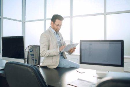 businessman with digital tablet sitting on office Desk.