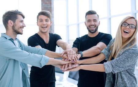 Foto de Gente de negocios sonriente con la mano apilada durante la reunión en la oficina creativa - Imagen libre de derechos