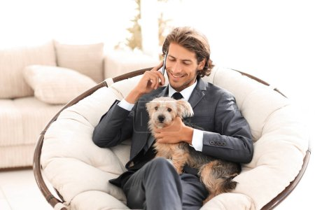 businessman is holding his pet and talking on a smartphone