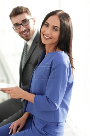cheerful business couple looking at file indoors.