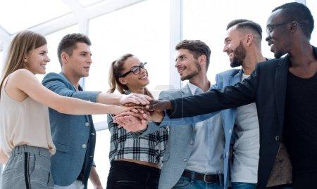 Photo pour Concept d'affaires, au démarrage, geste, gens et travail d'équipe - joyeuse équipe créative avec les mains sur le dessus de l'autre au bureau - image libre de droit
