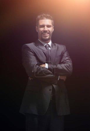 Photo pour Vue arrière .souriant homme d'affaires regardant la camera.isolated sur un fond noir . - image libre de droit
