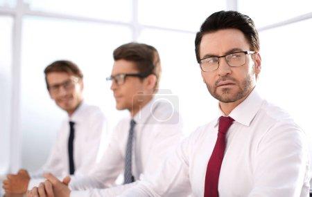 Photo pour Groupe de collègues sérieux assis à la notion de .des table bureau - image libre de droit