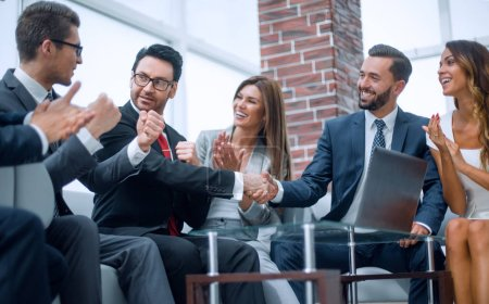 colleagues applaud business partners at a business meeting