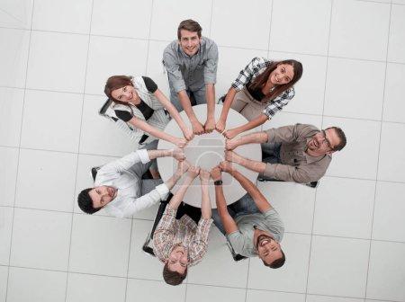 Photo pour Top view.the souriant équipe d'affaires plié les mains formant un cercle.the concept de travail d'équipe - image libre de droit