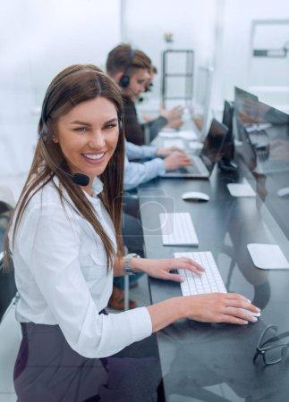 Photo pour Side view.smiling employé du centre d'appels sur le lieu de travail - image libre de droit