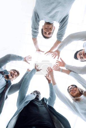 Photo pour Souriant équipe d'affaires debout dans un cercle. le concept d'unité - image libre de droit