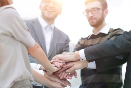 Teamwork concept.Business team standing joining hands together in the office.