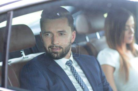 Photo pour Homme d'affaires regardant par la fenêtre, assis sur le siège arrière d'une voiture . - image libre de droit