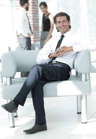 Photo pour Sourire d'homme d'affaires assis dans la chaise de bureau sur fond flou. - image libre de droit