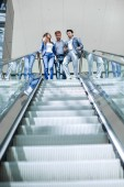 group of young businessmen standing at the beginning of the escalator