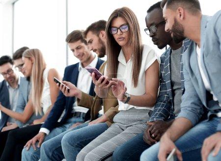 Groupe de jeunes gens en regardant les écrans de leurs smartphones