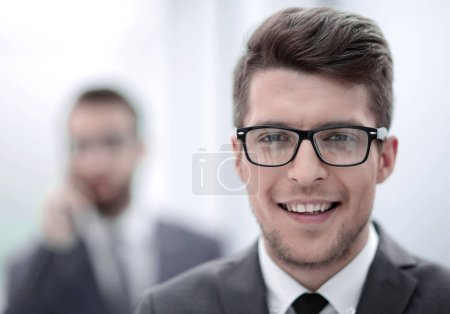 close up.smiling young businessman in the office background