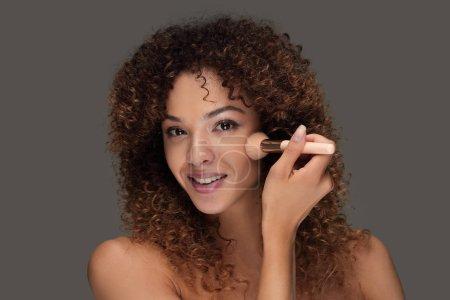 Photo pour Belle jeune femme avec un pinceau de maquillage. beauté et santé - image libre de droit