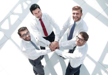 Foto de Vista superior. equipo de negocios poniendo su concepto de together.the de las manos del trabajo en equipo - Imagen libre de derechos