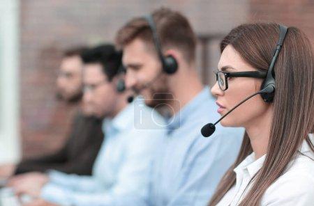 Photo pour Side view.the opérateur de centre d'appels et ses collègues travaillent dans le bureau. concept d'entreprise - image libre de droit