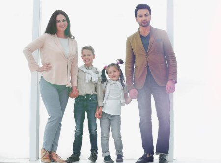 Photo for Portrait of a modern family standing near a large window .photo with copy space - Royalty Free Image