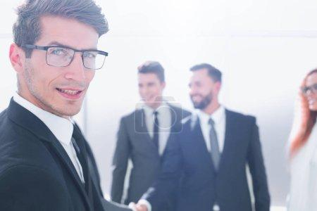 Foto de Primer plano. Hombre de negocios exitoso de pie en la oficina. concepto de negocio - Imagen libre de derechos