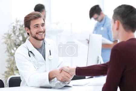 Photo pour Poignée de main entre médecin et patient assis au bureau - image libre de droit