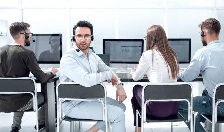 Photo pour Homme d'affaires avec un casque et ses collègues assis dans le bureau. photo avec espace de copie - image libre de droit