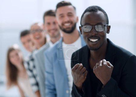 Photo pour Regarder la caméra avec divers collègues à l'arrière-plan, heureux jeune manager noir, entraîneur professionnel ou membre de l'équipe posant, tête tourné portrai - image libre de droit