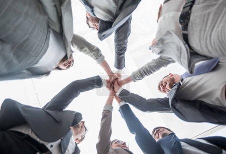 Photo pour Vue du bas. équipe d'affaires montrant leur unité.le concept de travail d'équipe - image libre de droit