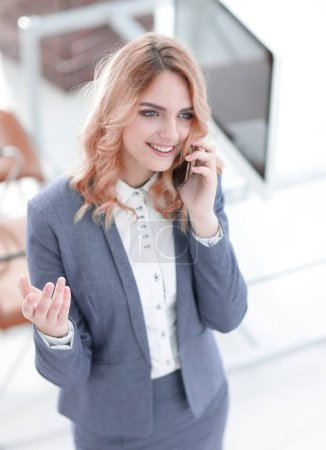 Photo for Closeup.a happy employee is talking on the smartphone .photo with copy space. - Royalty Free Image