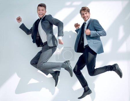 Photo pour Succès de deux hommes d'affaires en suit.they sont heureux et sauter sur fond isolé. Concept d'entreprise, Concept de style de vie - image libre de droit