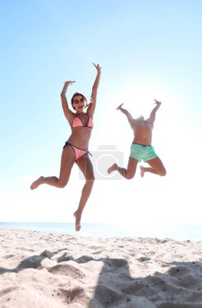 Photo for Picture of happy couple jumping on the beach. - Royalty Free Image
