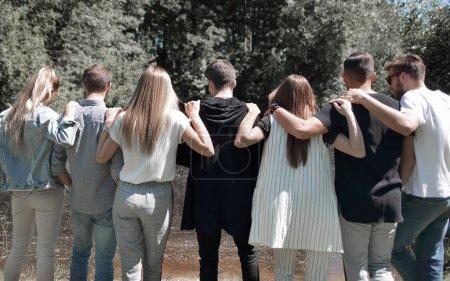 Photo pour Vue arrière. un groupe de jeunes marchant dans le parc. Le concept de team building - image libre de droit