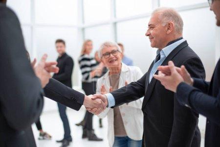 Photo pour Des gens d'affaires serrent la main à la réunion devant leurs collègues - image libre de droit