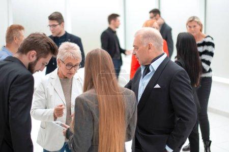 Photo pour Groupe de gens d'affaires modernes discutant pendant la pause-café debout dans le hall d'entrée du bureau - image libre de droit