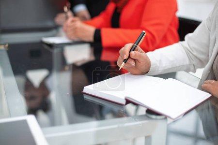 Photo pour Fermez les mains des femmes sur le bureau et écrivez à la plume sur le carnet de notes à la réunion - image libre de droit