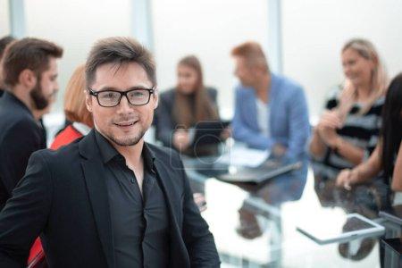 Photo pour Beau homme d'affaires souriant portant des lunettes assis à la réunion et regardant la caméra - image libre de droit